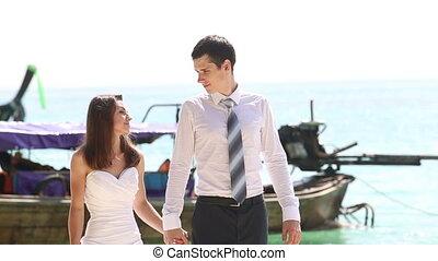 bride and groom walk looking into eyes along beach