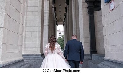 bride and groom walking in the city near a theatre