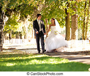 Bride and groom walking at park holding hands