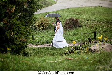 Bride and groom walking at park on rainy day