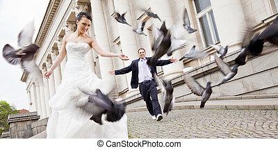 Bride and groom walking behind doves