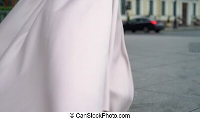 Bride and groom walking in a city at rainy cloudy day. Center of european town. Newlyweds going on a street, dress waving in slowmotion