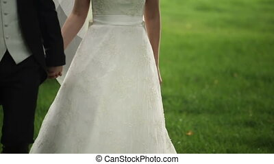 bride and groom walking in a field holding hands