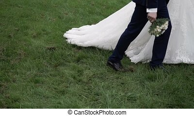 Bride and groom walking in a park at summer