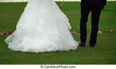 Bride and groom walking in park at the evening