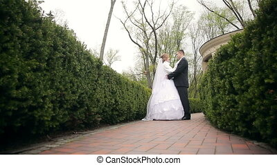 Bride and groom walking in park