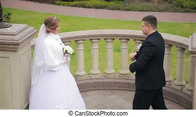 Bride and groom walking in park
