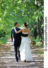 Bride and groom walking into distance together down country...
