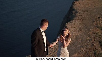 Bride and groom walking on mountain at sunset near sea