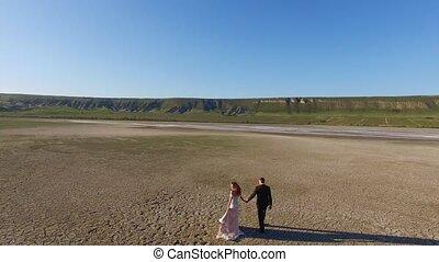 Bride and groom walking on texture ground. Dry salt lake....