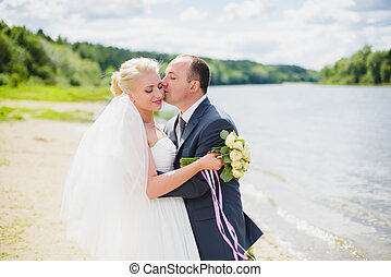 Bride and groom walking on the river
