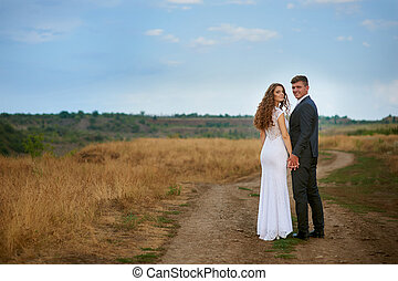 bride and groom walking on the road in a field