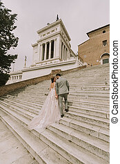 Bride and groom walking outdoors at Spagna Square and...