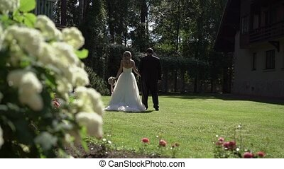 Bride and groom walking on lawn