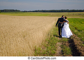 bride and groom walking in the fields