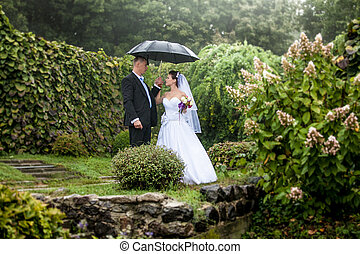 Bride and groom walking under umbrella at park