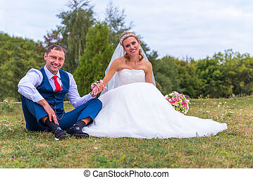 Bride and groom wedding sitting on the grass