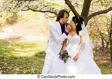 Bride and groom with a bouquet of kisses on the nature