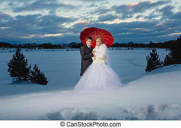 Bride and groom with big red umbrella