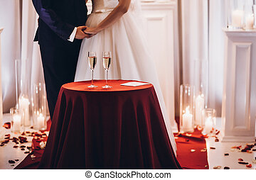 bride and groom with champagne glasses on red table at evening wedding ceremony reception, with lights on background. space for text.