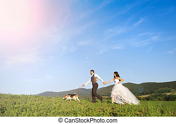 Bride and groom with dog - Bride and groom walk their beagle...