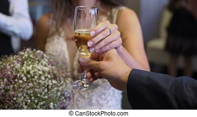 Bride and groom with glass of sparkling wine at the party