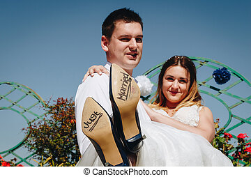 Bride and groom with 'Just Married' written on shoe soles, Rome cityscape in the background, Italy