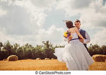 bride and groom with veil near hay