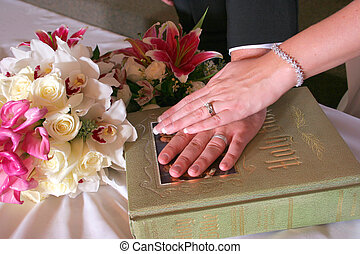 Bride and Grooms hands on bible on wedding day - Bride and...