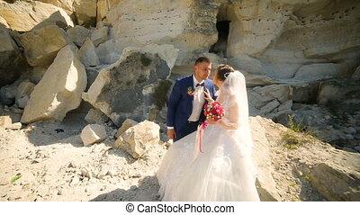 Bride and handsome groom walking near sandy rocks