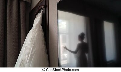 Bride and wedding dress in bedroom
