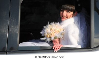 bride and with bouquet of roses waves hand from car - bride...