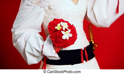 bride at wedding dress in folk style holding bouquet of...