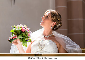 Bride at wedding in church with flower bouquet