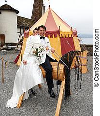Bride Behind Groom On Wooden Horse
