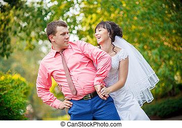 bride behind the groom in park