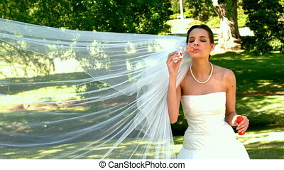Bride blowing bubbles in the park