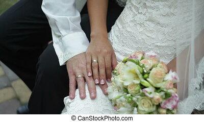 Bride caresses groom's hand near a bridal bouquet