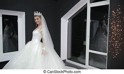 Young beautiful bride with a crown on head chic magnificent white wedding dress that drags on ground. Woman posing for camera. Long shot