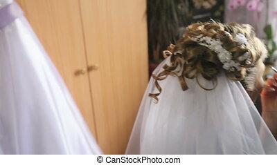 bride doing makeup and wedding dress weighs