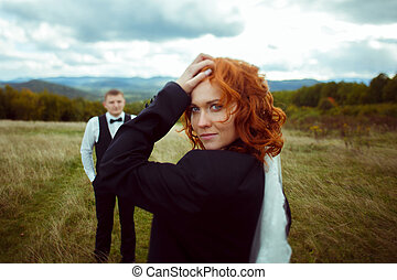 Bride dressed in groom's jacket looks over her shoulder stunning while he waits behind her