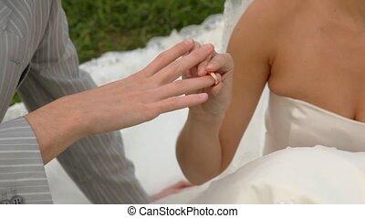 bride dresses gold ring on finger of groom close up