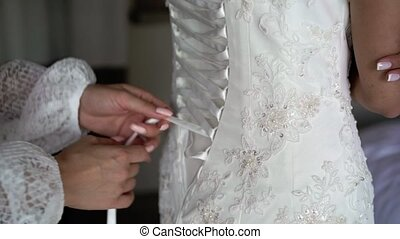 Bride dressing in wedding dress