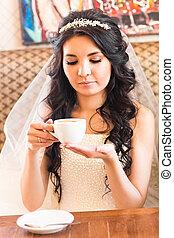 Bride drinking coffee at a wedding day