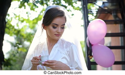 Bride drinking coffee at a wedding day