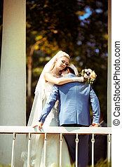 Bride embraces her beloved groom in the park