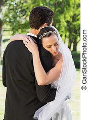 Bride embracing groom on wedding day