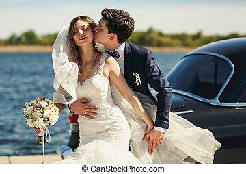 Bride enjoys a moment while groom bites her ear