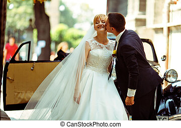 Bride enjoys groom's kiss standing in the front of an old car
