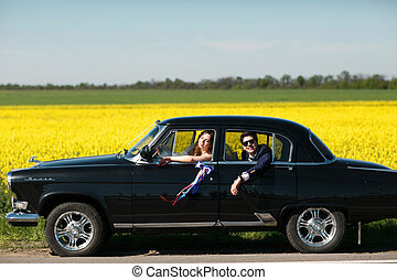 Bride enjoys sunshine driving a car while groom sits on the back seat